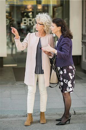 Full length senior women searching direction on digital tablet at city street Stock Photo - Premium Royalty-Free, Code: 698-07635395