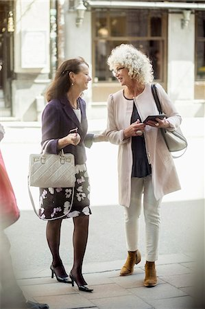 senior lady walking - Happy senior female friends talking while walking on street Stock Photo - Premium Royalty-Free, Code: 698-07635397