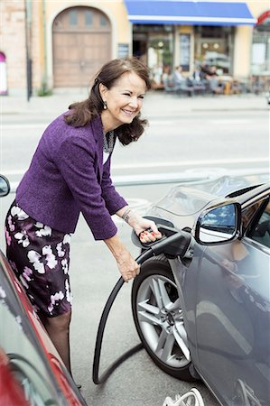 Smiling senior woman refueling car on street Stock Photo - Premium Royalty-Free, Code: 698-07635399