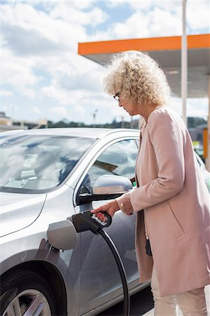 Side view of senior woman refueling car at gas station Stock Photo - Premium Royalty-Free, Code: 698-07635400