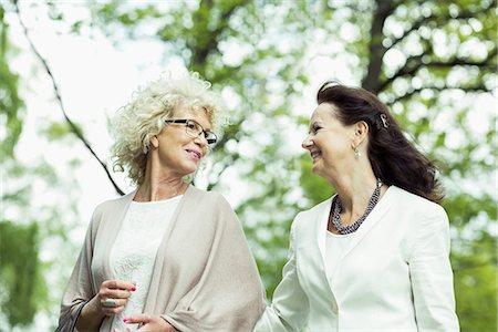 Happy senior women talking while walking in park Stock Photo - Premium Royalty-Free, Code: 698-07635415