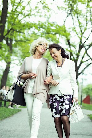 senior lady walking - Happy senior female friends walking on garden path Stock Photo - Premium Royalty-Free, Code: 698-07635417