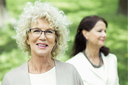Portrait of smiling senior woman at park with friend in background Stock Photo - Premium Royalty-Free, Code: 698-07635418