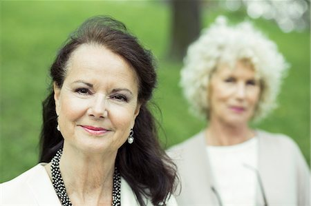 Portrait of confident senior woman at park with friend in background Stock Photo - Premium Royalty-Free, Code: 698-07635421