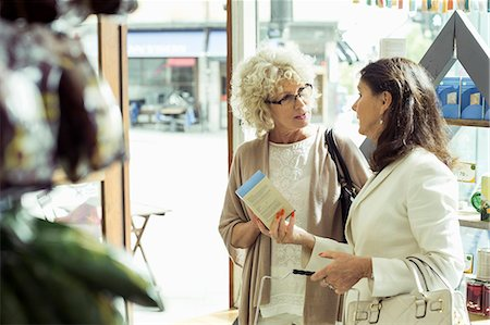 Senior women discussing over product in store Stock Photo - Premium Royalty-Free, Code: 698-07635431