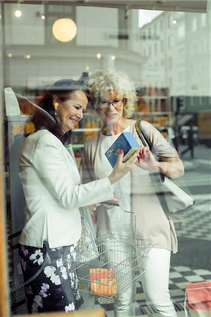 Smiling senior women reading instructions on product in store Stock Photo - Premium Royalty-Free, Code: 698-07635433