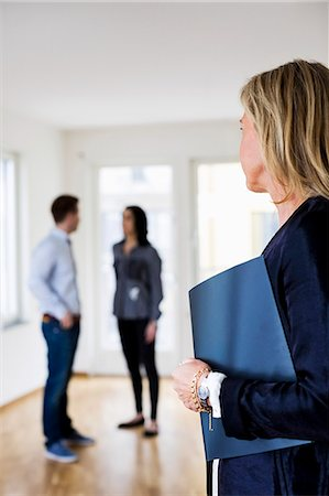 Mature real estate agent looking at couple discussing at home Stock Photo - Premium Royalty-Free, Code: 698-07635444