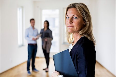renting - Portrait of confident female real estate agent with couple standing in background at home Stock Photo - Premium Royalty-Free, Code: 698-07635445
