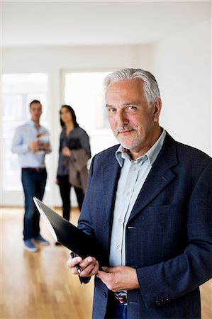 Portrait of confident male real estate agent with couple standing in background at home Stock Photo - Premium Royalty-Free, Code: 698-07635446