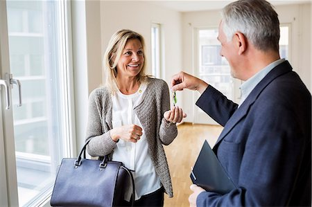 renting - Happy male real estate agent giving keys to woman in new house Stock Photo - Premium Royalty-Free, Code: 698-07635448