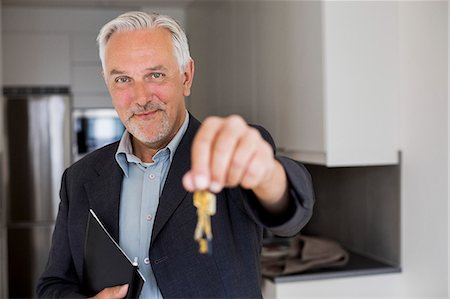 Portrait of confident real estate agent holding new house keys Stock Photo - Premium Royalty-Free, Code: 698-07635449