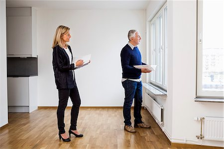 flat (apartment) - Mature real estate agents looking through window at home Stock Photo - Premium Royalty-Free, Code: 698-07635440