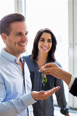 purchase - Cropped image of real estate agent handing over keys to couple in new house Stock Photo - Premium Royalty-Free, Code: 698-07635441