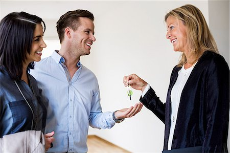 Happy real estate agent giving keys to couple in new house Stock Photo - Premium Royalty-Free, Code: 698-07635442