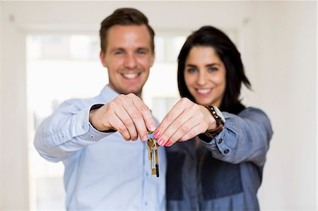 purchase - Portrait of happy couple holding keys in new house Stock Photo - Premium Royalty-Free, Code: 698-07635443