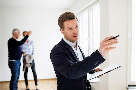 Real estate agent examining house with couple discussing in background Stock Photo - Premium Royalty-Free, Code: 698-07635454