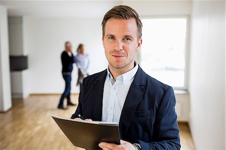 displaying - Portrait of confident real estate agent with couple standing in background at home Stock Photo - Premium Royalty-Free, Code: 698-07635455