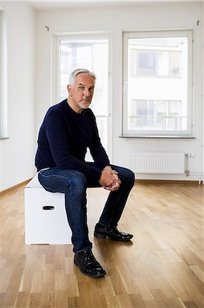Full length portrait of confident man sitting on moving box in new house Stock Photo - Premium Royalty-Free, Code: 698-07635456