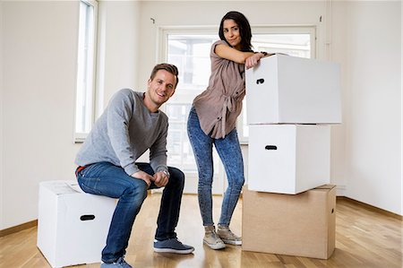 Full length of happy couple with moving boxes at home Stock Photo - Premium Royalty-Free, Code: 698-07635458