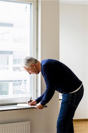 renting - Side view of businessman writing at window sill at home Stock Photo - Premium Royalty-Free, Code: 698-07635450