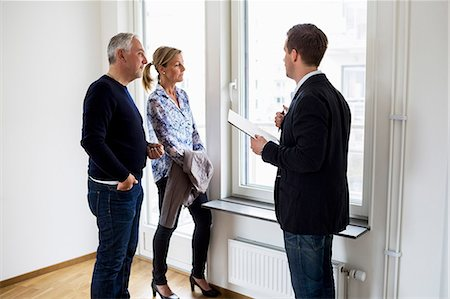 flat - Male real estate agent discussing with couple at home Stock Photo - Premium Royalty-Free, Code: 698-07635453