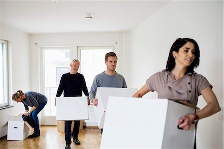renting - Family of four with cardboard boxes moving into new house Stock Photo - Premium Royalty-Free, Code: 698-07635464