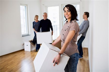 renting - Family of four with cardboard boxes moving into new house Stock Photo - Premium Royalty-Free, Code: 698-07635465