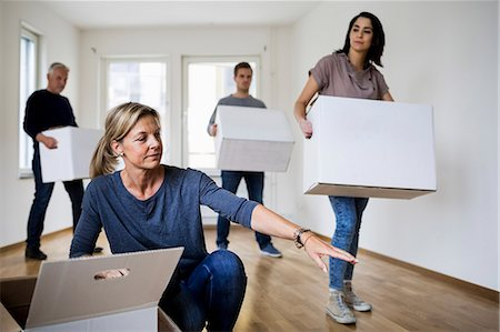 renting - Family of four with cardboard boxes moving into new house Stock Photo - Premium Royalty-Free, Code: 698-07635466