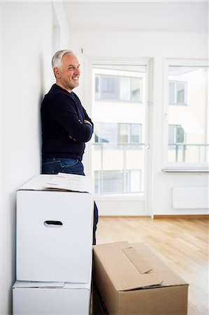 Side view of mature man standing by moving boxes at home Stock Photo - Premium Royalty-Free, Code: 698-07635468