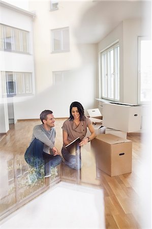 flat (apartment) - Full length of couple reading brochure into their new house Stock Photo - Premium Royalty-Free, Code: 698-07635469
