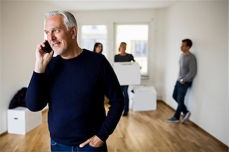 Mature man using mobile phone while family with moving boxes in background at home Stock Photo - Premium Royalty-Free, Code: 698-07635462