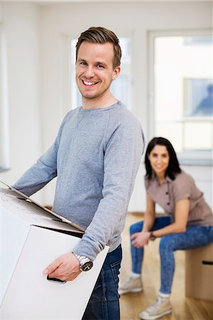 Portrait of happy man carrying cardboard box with woman in background at home Stock Photo - Premium Royalty-Free, Code: 698-07635474