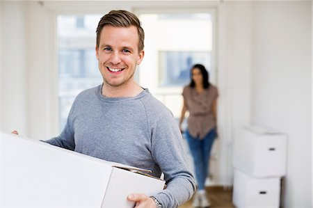Portrait of happy man carrying moving box with woman in background at home Stock Photo - Premium Royalty-Free, Code: 698-07635475