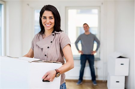 renting - Portrait of happy woman carrying moving box with man in background at home Stock Photo - Premium Royalty-Free, Code: 698-07635476