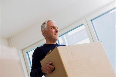 Mature man carrying moving box at home Stock Photo - Premium Royalty-Free, Code: 698-07635478