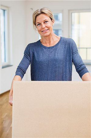 renting - Portrait of happy mature woman carrying moving box at home Stock Photo - Premium Royalty-Free, Code: 698-07635479