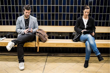 platform - Full length of people using technologies on bench at subway station Stock Photo - Premium Royalty-Free, Code: 698-07635487