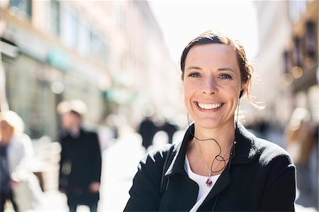 Portrait of smiling mature businesswoman listening to music on city street Stock Photo - Premium Royalty-Free, Code: 698-07635489