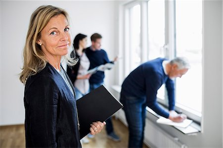 displaying - Portrait of confident mature real estate agent with colleague and couple at home Stock Photo - Premium Royalty-Free, Code: 698-07635482
