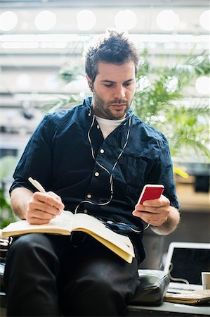 Mid adult businessman using mobile phone while writing in book at cafe Stock Photo - Premium Royalty-Free, Code: 698-07635506