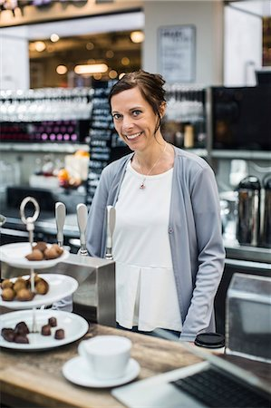 europe coffee shop - Portrait of smiling mature female owner at cafe counter Stock Photo - Premium Royalty-Free, Code: 698-07635514