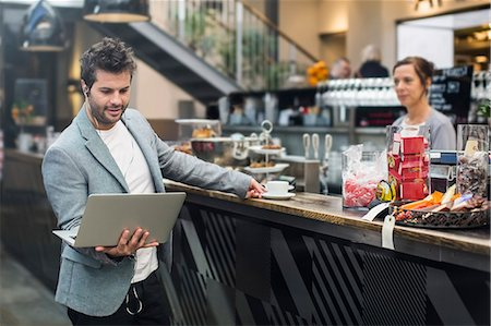 europe coffee shop - Mid adult man holding laptop while buying coffee at cafe Stock Photo - Premium Royalty-Free, Code: 698-07635515