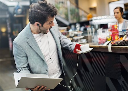 Panic mid adult man holding laptop and coffee at cafe Stock Photo - Premium Royalty-Free, Code: 698-07635516