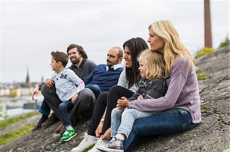 Homosexual families relaxing on rock at lakeshore Stock Photo - Premium Royalty-Free, Code: 698-07635524