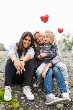 Portrait of happy female homosexual family relaxing on rock Stock Photo - Premium Royalty-Free, Code: 698-07635525