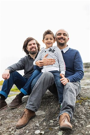 Portrait of happy male homosexual family relaxing on rock Stock Photo - Premium Royalty-Free, Code: 698-07635526