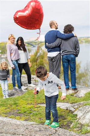 Boy holding balloon on rock with homosexual families in background Stock Photo - Premium Royalty-Free, Code: 698-07635522
