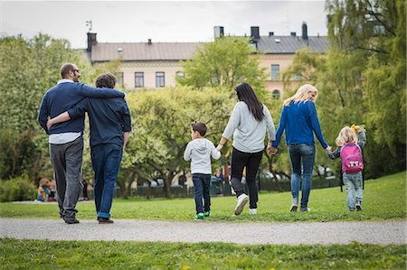 Rear view of female homosexual family walking at park with gay couple in background Stock Photo - Premium Royalty-Free, Code: 698-07635533