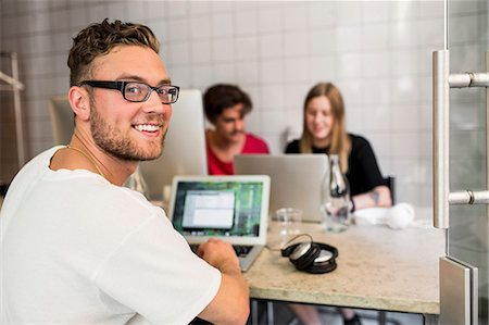 designer - Portrait of happy young businessman with colleagues in background at creative office Stock Photo - Premium Royalty-Free, Code: 698-07635546
