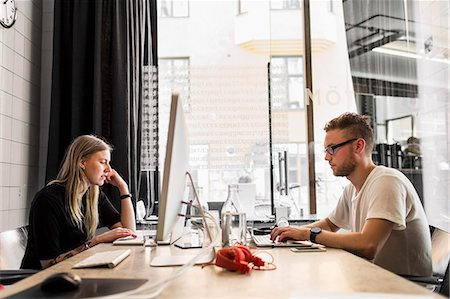 Side view of young businessman and businesswoman working in new office Stock Photo - Premium Royalty-Free, Code: 698-07635547